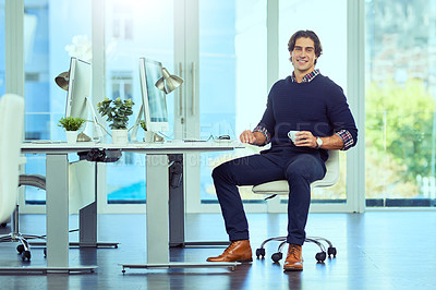 Buy stock photo Shot of a young businessman working at his desk in a modern office