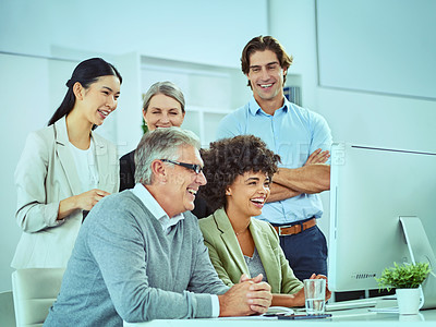 Buy stock photo Shot of a group of businesspeople using a computer together in a modern office