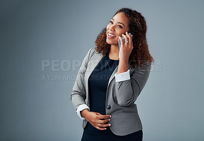 Buy stock photo Studio shot of a young businesswoman talking on a cellphone against a grey background