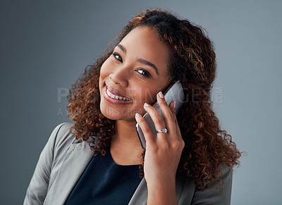 Buy stock photo Studio portrait of a young businesswoman talking on a cellphone against a grey background