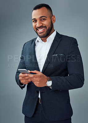 Buy stock photo Studio portrait of a young businessman using a cellphone against a grey background