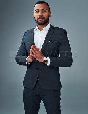 Buy stock photo Studio portrait of a young businessman posing with his hands together against a grey background