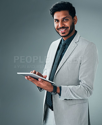 Buy stock photo Studio portrait of a young businessman using a digital tablet against a grey background