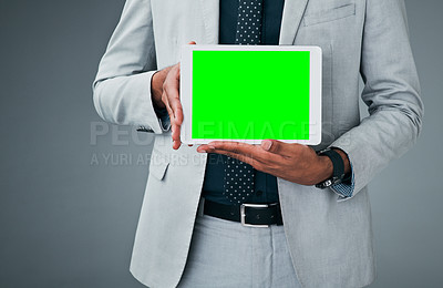 Buy stock photo Closeup shot of an unrecognizable businessman holding up a digital tablet with a green screen against a grey background