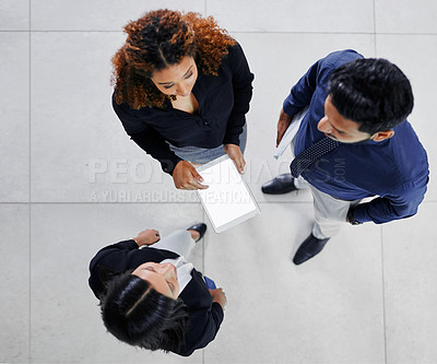 Buy stock photo High angle shot of three young businesspeople talking while standing in their office lobby