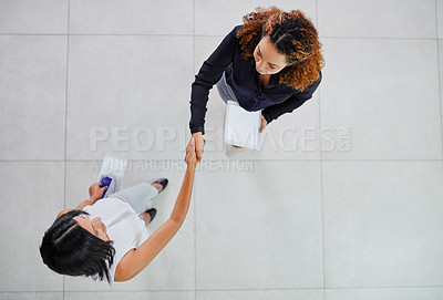 Buy stock photo High angle shot of two young businesswomen shaking hands while standing in their office lobby