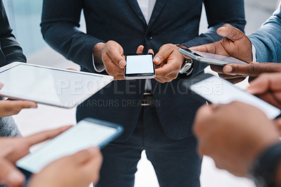 Buy stock photo High angle shot of a group of unrecognizable businesspeople using wireless devices while standing in their office lobby