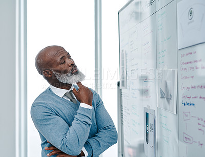 Buy stock photo Shot of a mature businessman brainstorming with notes on a whiteboard in an office