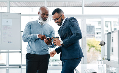 Buy stock photo Shot of a businessman showing his colleague something on his cellphone in an office