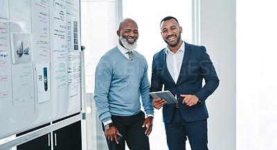 Buy stock photo Portrait of two businessmen using a digital tablet together in an office