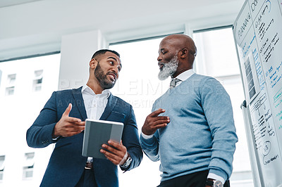 Buy stock photo Low angle shot of two businessmen using a digital tablet together in an office