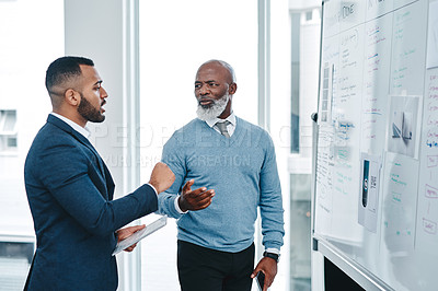 Buy stock photo Shot of two businessmen brainstorming together on a whiteboard in an office