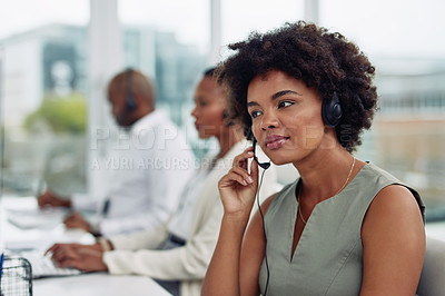 Buy stock photo Shot of a call centre agent working in an office alongside her colleagues
