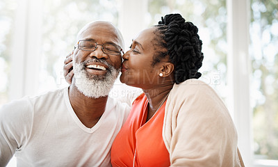 Buy stock photo Shot of a mature woman affectionately kissing her husband at home