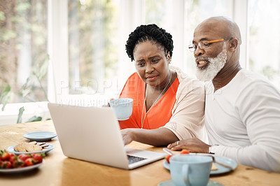 Buy stock photo Shot of a mature couple using a laptop while having breakfast together at home