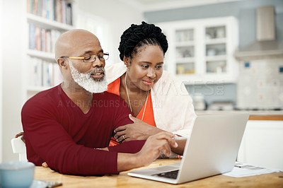 Buy stock photo Shot of a happy mature couple using a laptop together at home