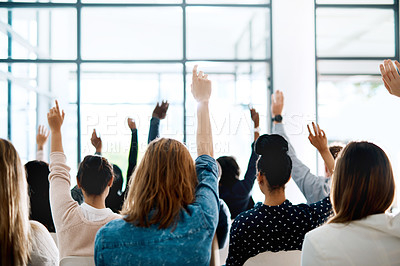 Buy stock photo Rearview shot of a group of businesspeople raising their hands to ask questions during a conference