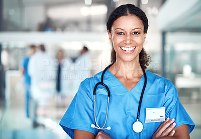 Buy stock photo Cropped portrait of an attractive female nurse standing with her arms folded in the hospital