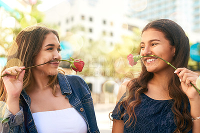 Buy stock photo Cropped shot of two female best friends being playful with roses in the city