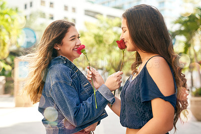 Buy stock photo Cropped shot of two female best friends being smelling roses in the city