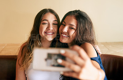 Buy stock photo Cropped shot of two attractive young women taking selfies in their local cafe