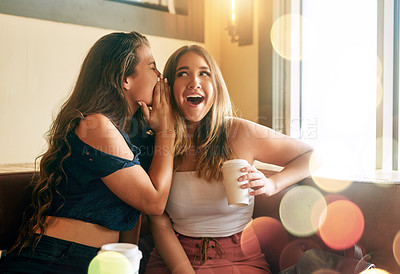 Buy stock photo Cropped shot of two attractive young women gossiping in their local cafe