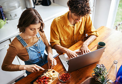 Buy stock photo Shot of a young man using his laptop while his girlfriend is busy cutting fruit