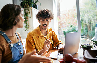 Buy stock photo Shot of a couple using their laptop while spending time together at home