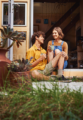 Buy stock photo Shot of a young couple siting in the doorway of their home