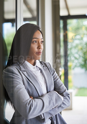 Buy stock photo Shot of an ambitious young businesswoman looking thoughtfully out of a window