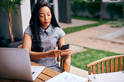 Buy stock photo Shot of an ambitious young businesswoman using a mobile phone at a table outdoors