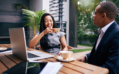 Buy stock photo Shot of a young businesswoman and businessman using a laptop while having a discussion over coffee outdoors
