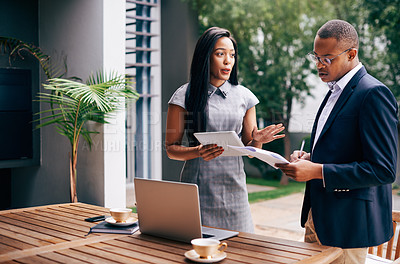 Buy stock photo Shot of a young businesswoman and businessman discussing paperwork together outdoors