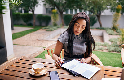Buy stock photo Shot of an ambitious young businesswoman making notes while sitting outdoors