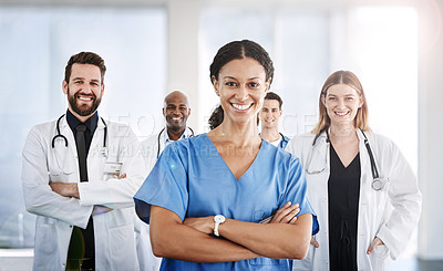 Buy stock photo Portrait of a confident doctor working at a hospital with her colleagues in the background