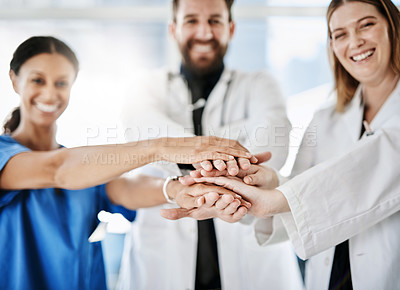 Buy stock photo Cropped shot of a team of doctors joining their hands together in unity