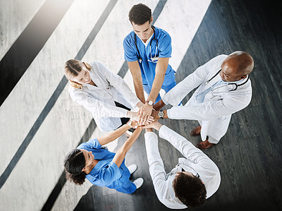 Buy stock photo Shot of a team of doctors joining their hands together in unity