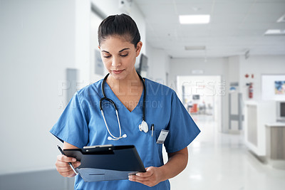 Buy stock photo Cropped shot of an attractive young female nurse going through medical records while working in the hospital