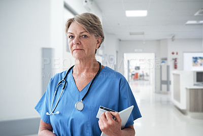 Buy stock photo Cropped portrait of a mature female nurse holding a tablet while working in the hospital
