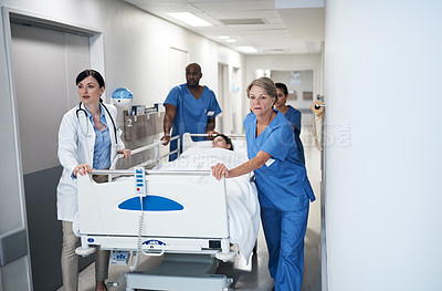Buy stock photo Cropped shot of a medical team pushing a patient down the hallway in a gurney
