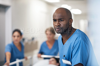Buy stock photo Cropped shot of a handsome mature male nurse and his team pushing a patient down the hallway in a gurney