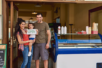 Buy stock photo Cropped portrait of an affectionate family of three standing in the entrance way to their ice cream shop