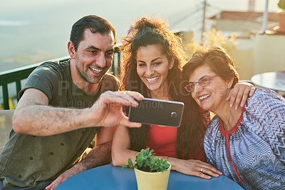 Buy stock photo Cropped shot of an affectionate family of three taking selfies while sitting outside