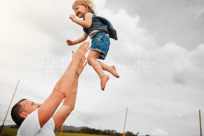 Buy stock photo Cropped shot of a mature man tossing his young daughter into the air and then catching her outside