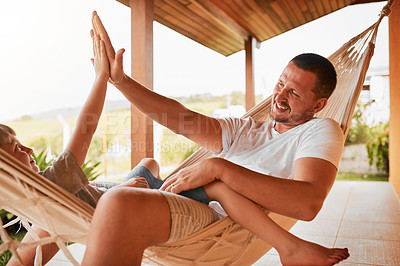 Buy stock photo Cropped shot of an mature man and his young son high fiving while lying outside on a hammock