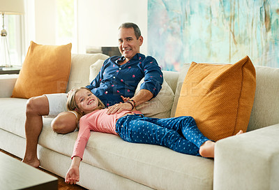 Buy stock photo Full length portrait of a mature man and his daughter on the sofa at home