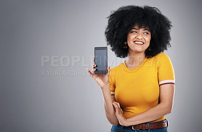 Buy stock photo Studio shot of an attractive young woman posing with a cellphone against a grey background