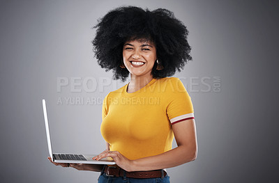 Buy stock photo Studio shot of an attractive young woman posing with a laptop against a grey background