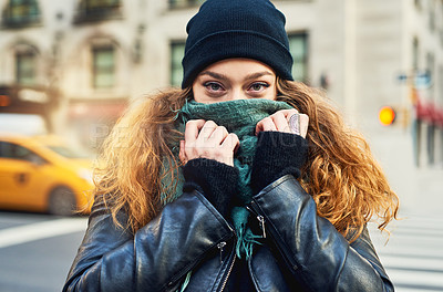 Buy stock photo Shot of a woman covering her mouth with her scarf while out in the city