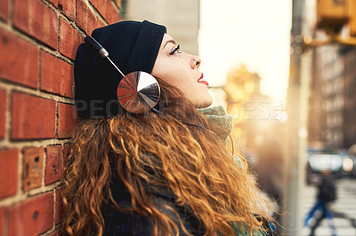 Buy stock photo Cropped shot of a young woman listening to music while leaning against a brick wall outside